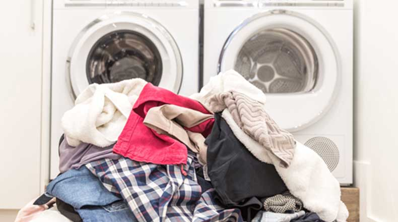 clothes piled up in front of a washer and dryer
