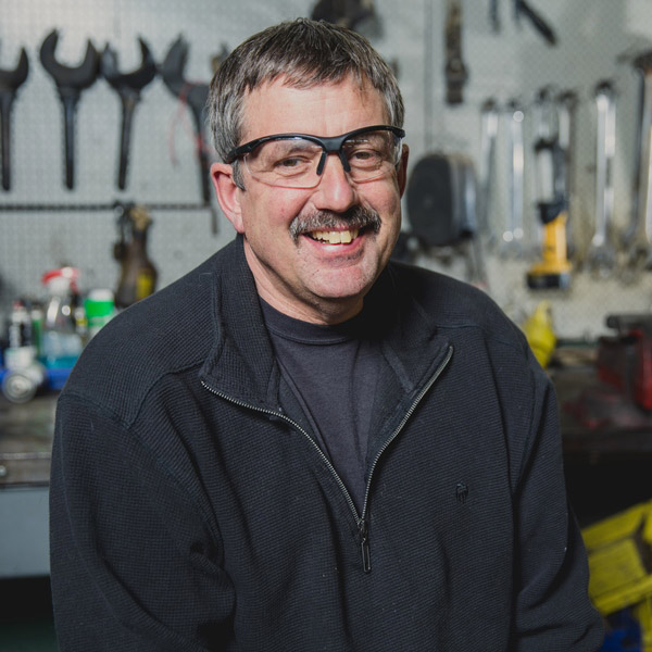 smiling man in goggles sits in front of tool bench