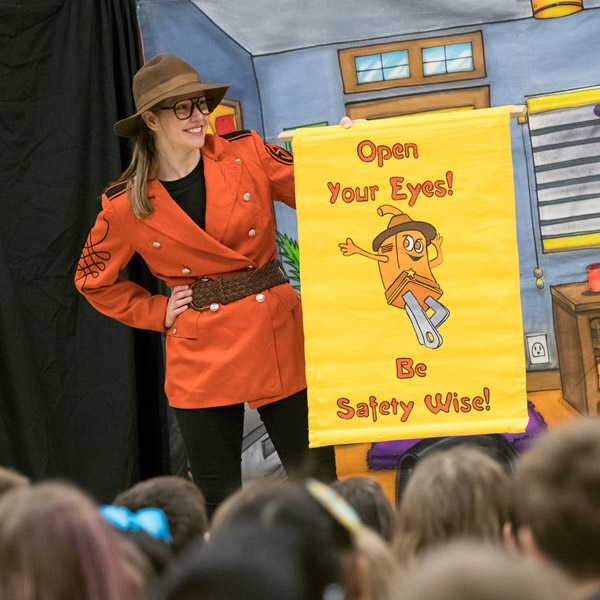 smiling young woman in sheriff costume appears in stage presentation for kids